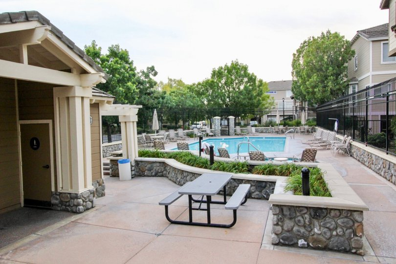 Inside the apartment in Huntington has swimming pool with seating chairs and tables with trees and closing umbrella