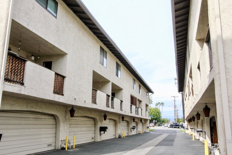 A street dividing buildings in Manana Townhomes with garages on a sunny day