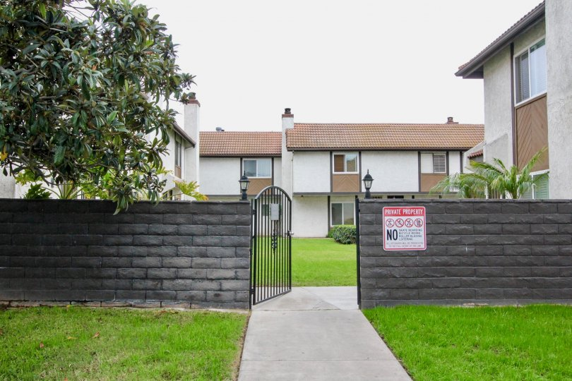 A gate to the Manana Townhomes with a gray brick fence