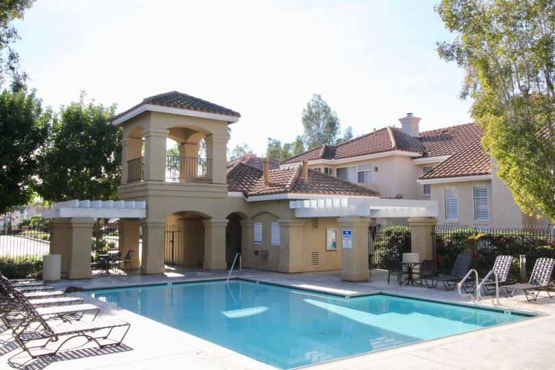 The swimming pool in the Montevista with the big light yellow and white color buldings, resting chairs, small trees, big trees.