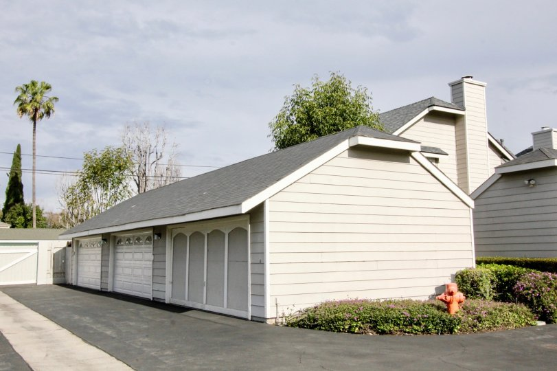A light grey color house and garage with bushes around them in the orange creek community in orange, california.