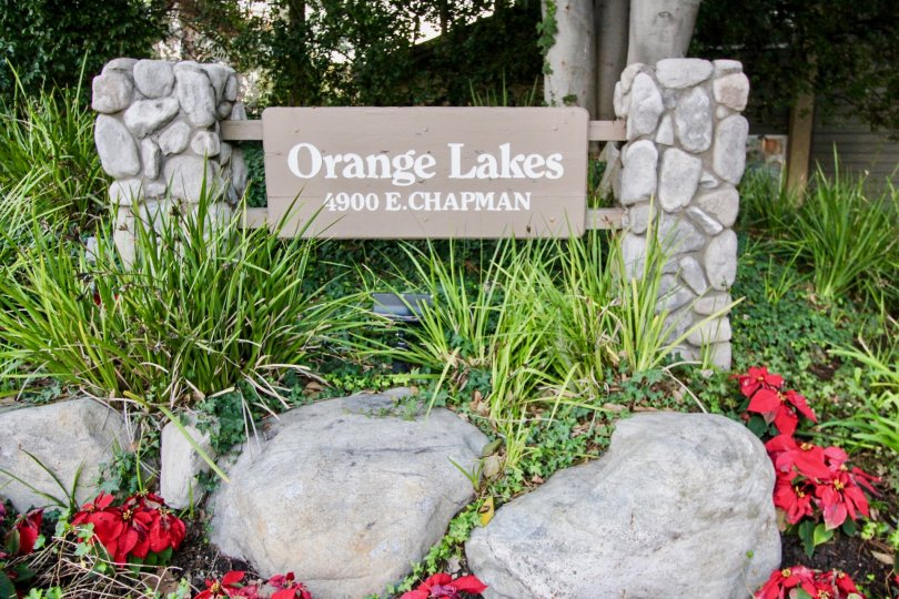 The Oranges Lakes community sign with flowers and plants