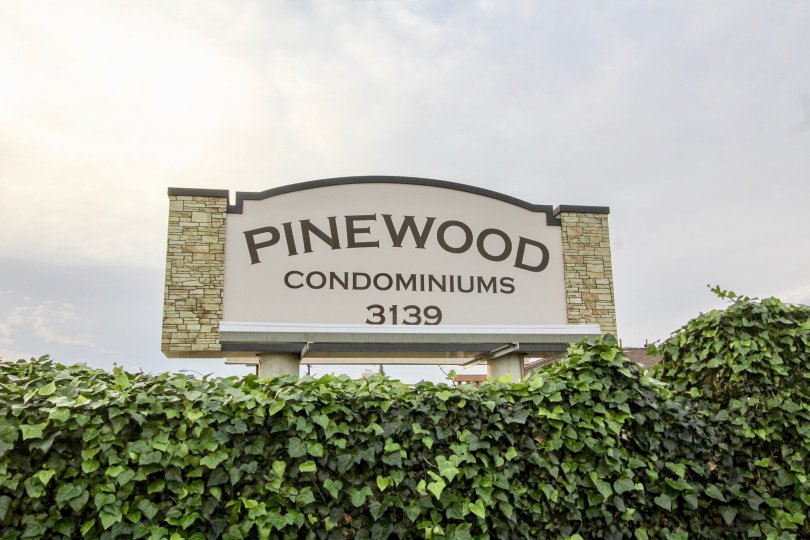 The pinewood condominiums sign in Orange, California, on a cloudy day.