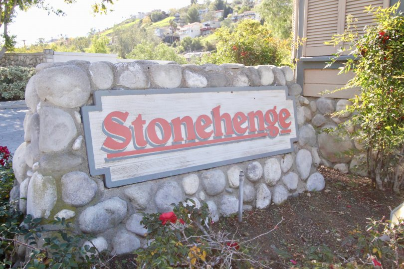 The stone sign for the Stonehenge community with flowers