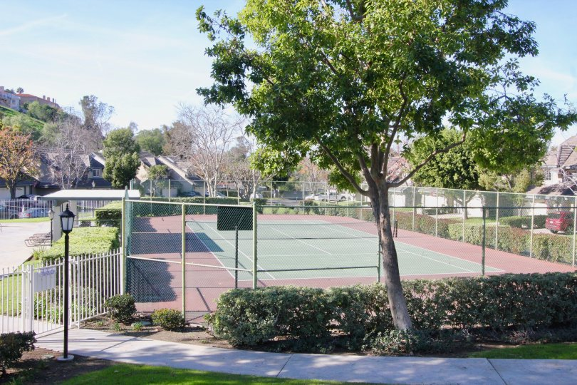 A lawn tennis court with an all round fence inside the Stonehenge community in orange city
