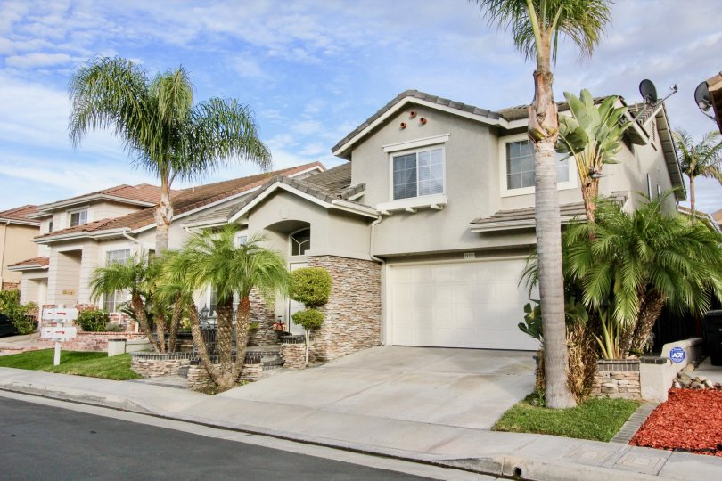 A gray home with palm trees in Sycamore Crossing on a sunny day