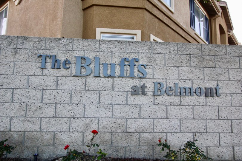 Brick wall with named of The Bluffs at Belmont, in blue, mounted on the wall with an apartment in the background