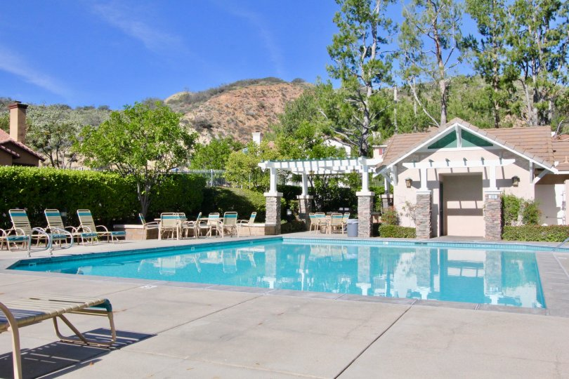 A pool in the Canyon Hills community with deck chairs and tables.