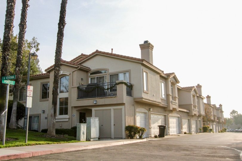 A sunny day by some Bella Ventana houses which all have multiple garages and windows visible, along with trees next to some