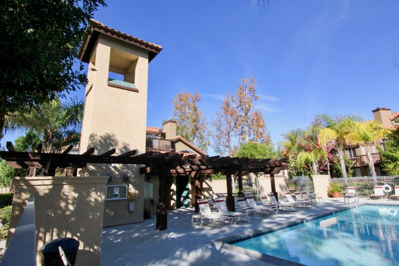 The poolhouse, lounge chairs and pool shaded by trees in the Brisa del Lago II community in Rancho Santa Margarita, CA