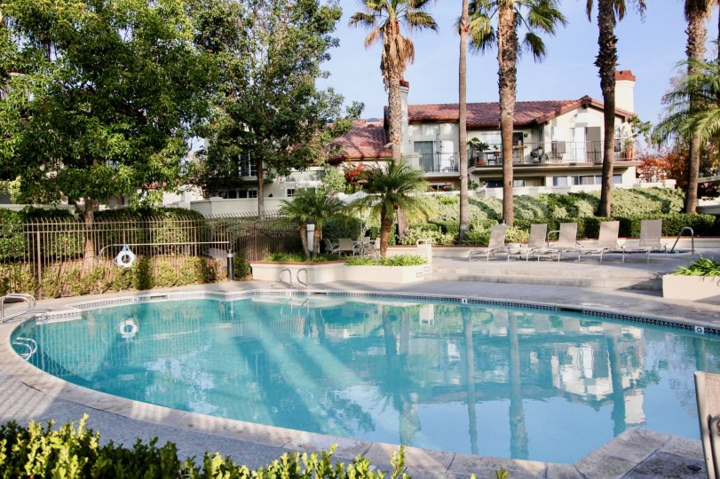 A still pool reflects a residential building in the Candelero community