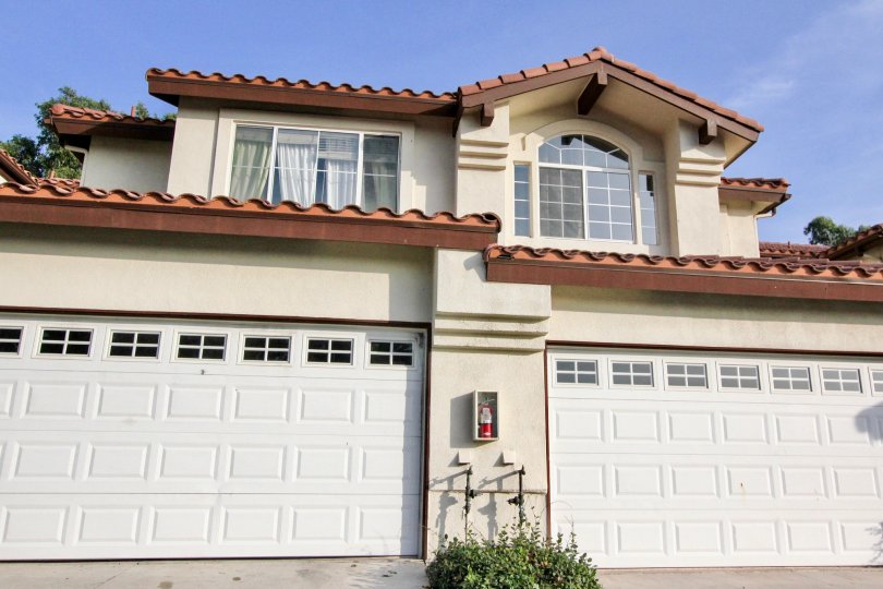 A tan home with red roof and two garages in Candelero community in Rancho Santa Margarita, California.