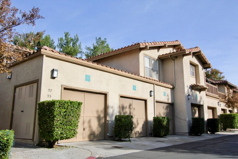Front view of residences in Sycmore Glen in Tustin, California. Single car garages and balconies for the residents.