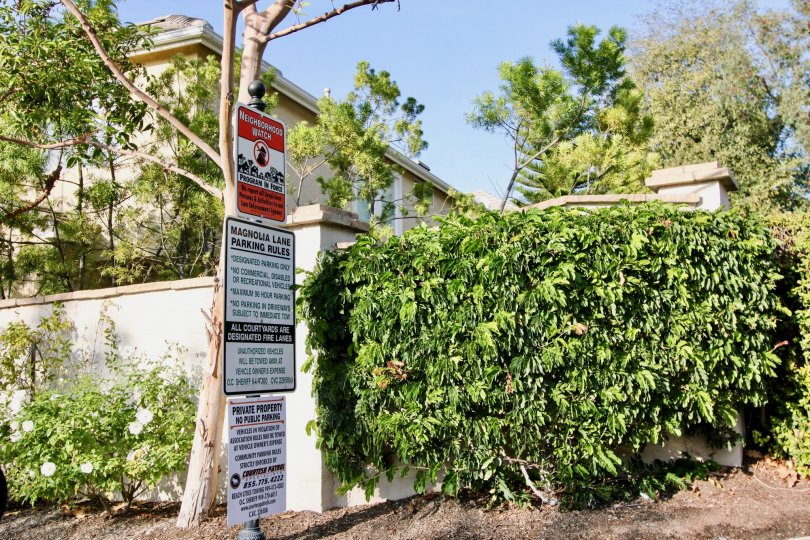 Green trees with sign boards near villa of Magnolia of Rancho Santa Margarita