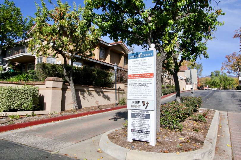 The entrance to Mission Courts community with a neighborhood rules and regulations sign and magnolia trees