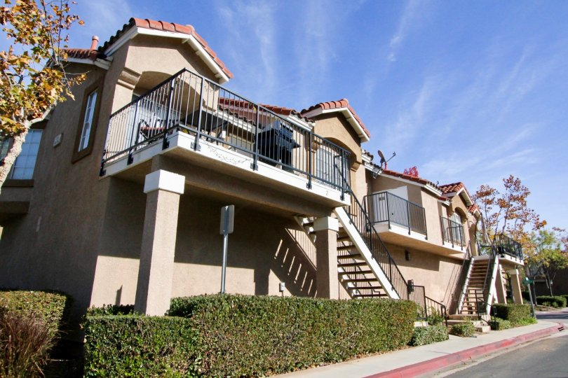 A sunny day at the Spanish style residences of Mission Courts with wrought iron railings and upstairs patios