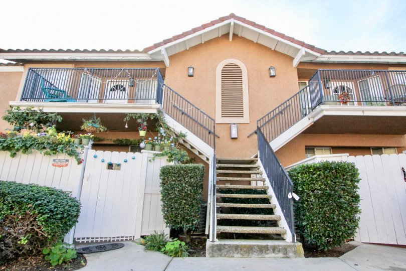 Two-storey townhouses with exterior staircase and orangish paint n the Mission Courts community.