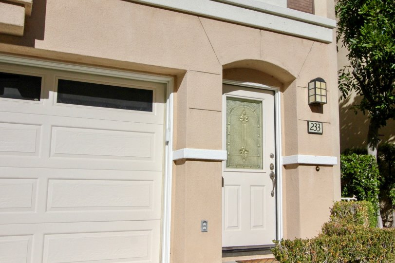 A low-rise residence painted in cream with closed carport in the Montana Del Lago community.