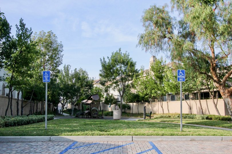 Two handicap parking signs sit in the grass near a brick driveway in Sea Country homes