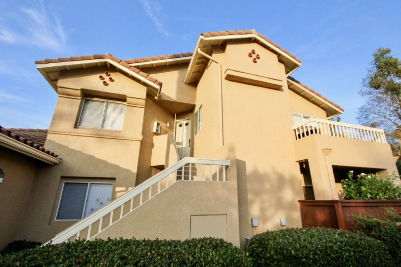 A sunny day by a Sierra Verde multiplex, painted a mostly tannish color with multiple stories and bushes in front of it