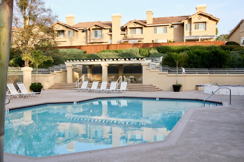 A lovely pool located in the Sierra Verde housing community where there are lounging chairs and a fence surrounding the pool area