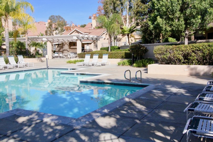A lovely pool located in the Sonoma Court housing community where there are lounging chairs and a fence surrounding the pool area