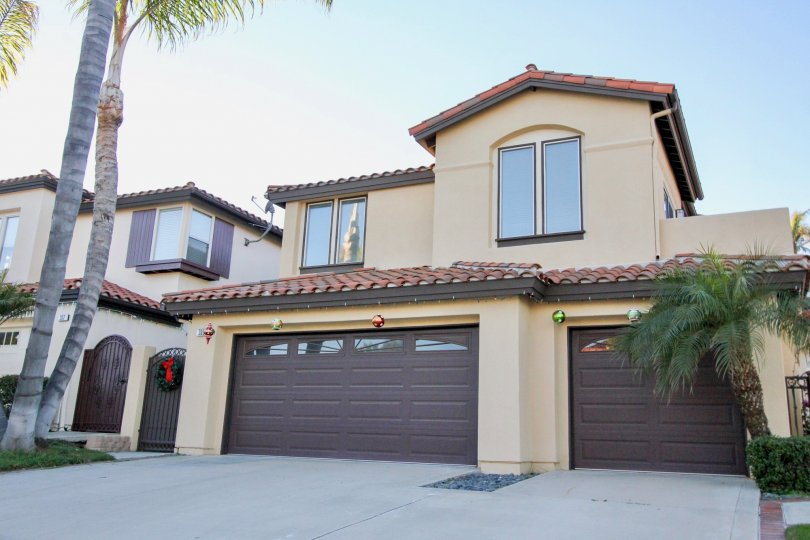 A two-storey residence with dark brown carport in the Del Cabo Estates community.