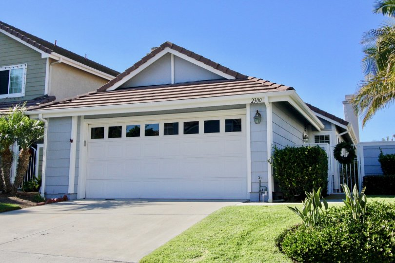 Bungalow style house with a double car attached garage and sizable front lawn with hedges