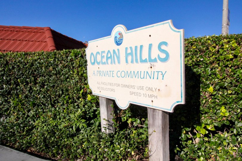 The sign of a private community called Ocean Hills surrounded by trimmed shrubbery in San Clemente, California