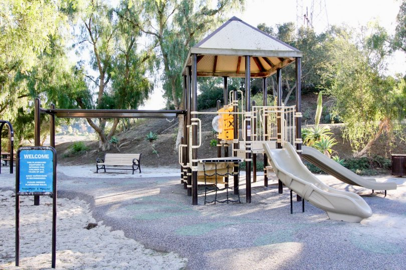 children's playground with white slides, bars, ropes, and bench for adults