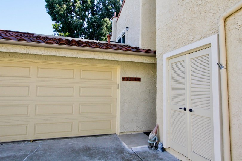 A closed carport with louvered back door access in the Sunset Village community.