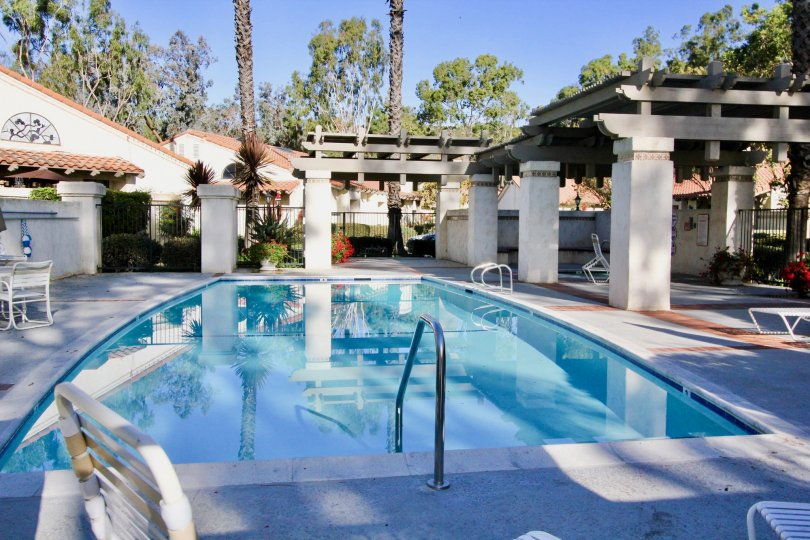 A pool with chairs and tables around it in Capistrano D'Oro community in San Juan Capistrano, California.