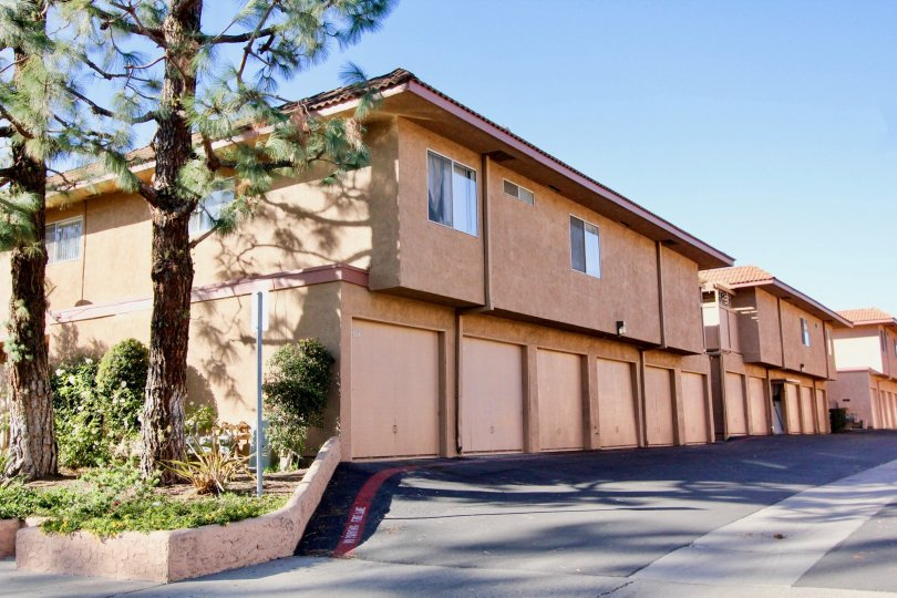 Salmon colored home with large windows and trees in the yard in Capistrano Villas.