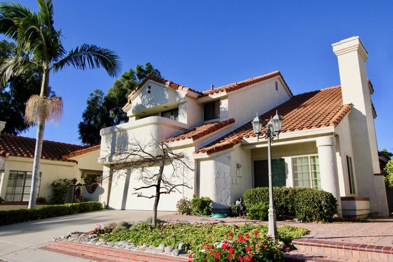 A two story white residential home with a tile roof in Casitas Del Rio in San Juan Capistrano in the state of California.