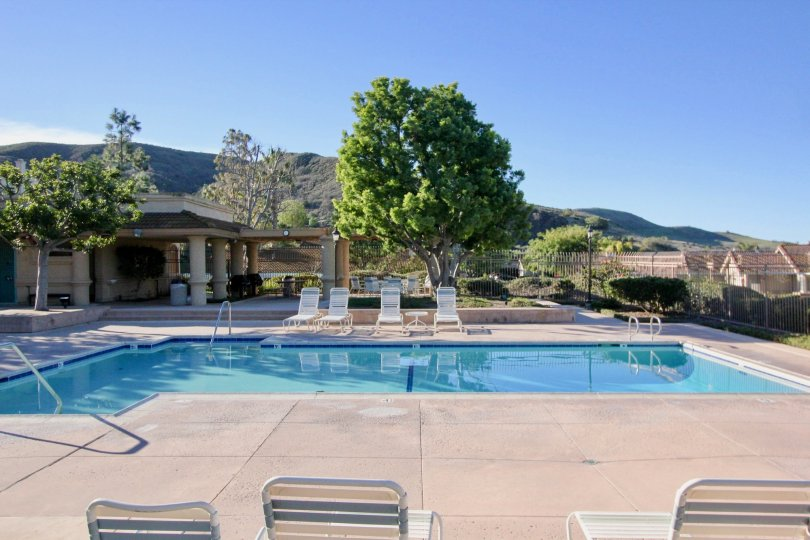 A medium pool with chairs and mountains in Loma Vista community in San Juan Capistrano, california.