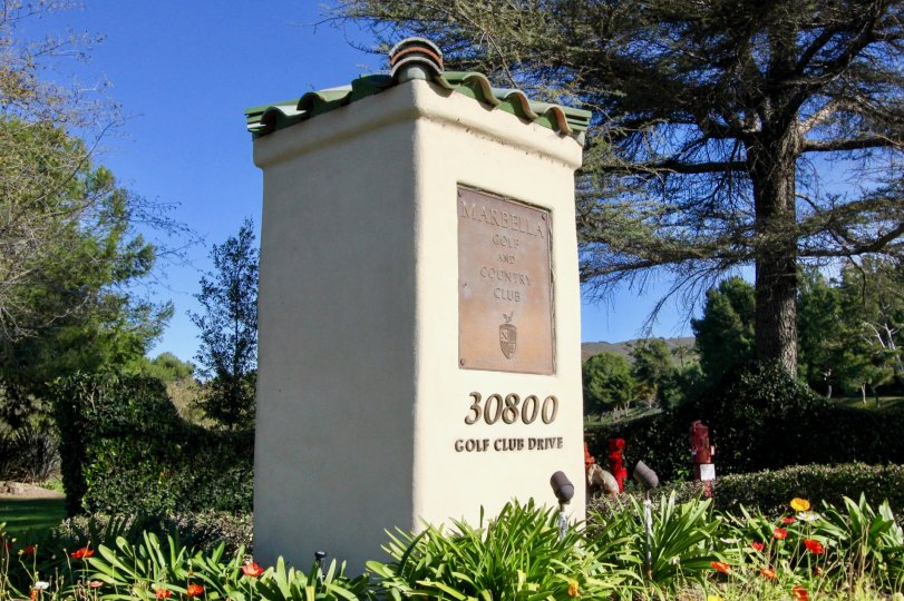 The entrance post to the Marbella Golf and Country Club with flowers, trees and greenery in San Juan Capistrano, CA