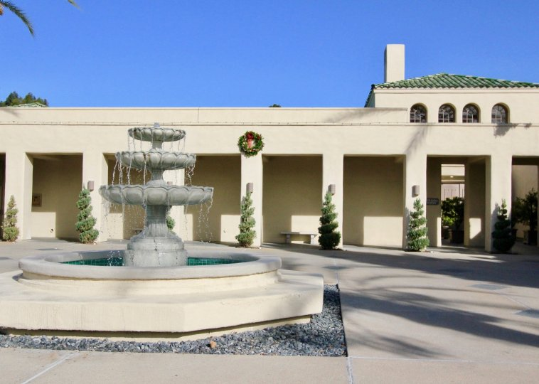 Flowing fountain in a courtyard of large building on a clear day