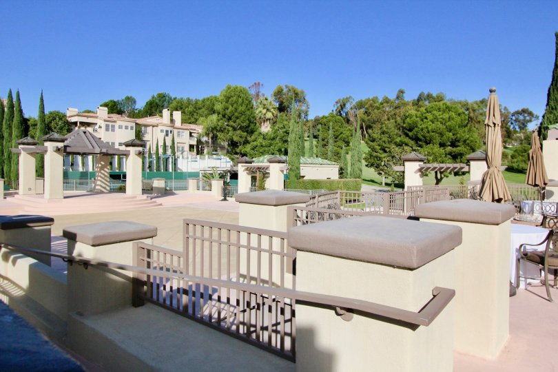 A tiled courtyard with decorative fences and closed umbrellas in the Marbella Golf Villas community.