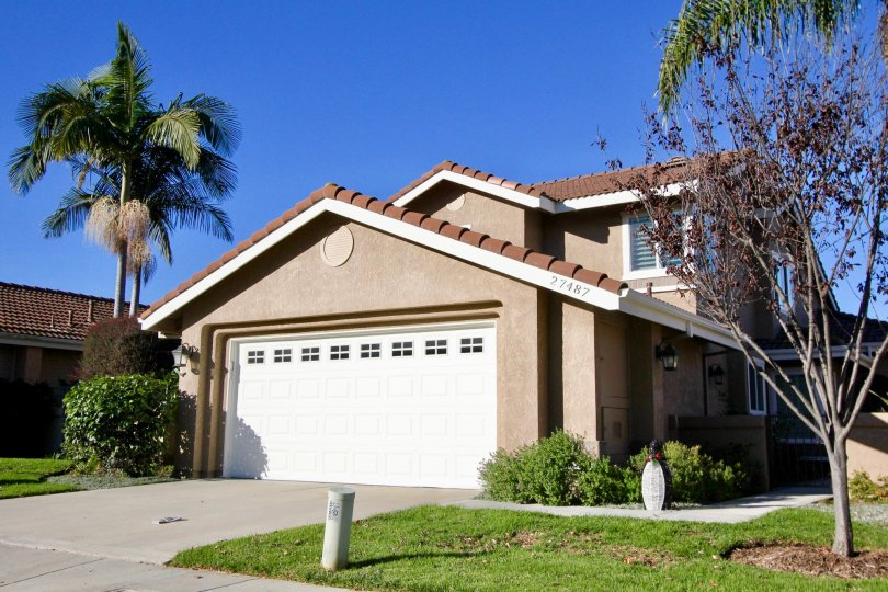 A sunny day in the area of Mesa Vista South, outside, garage, palm trees, grass, condo