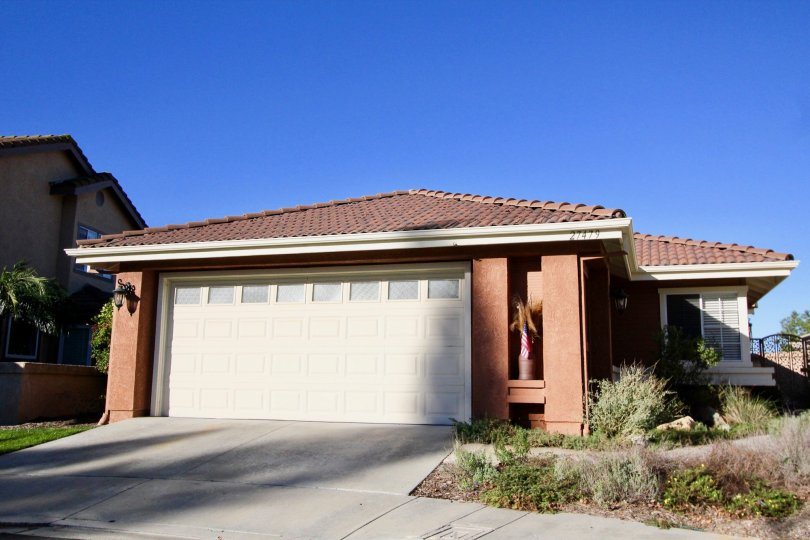 A potted palm tree sits in a nook on a garage of a homes at Mesa Vista South