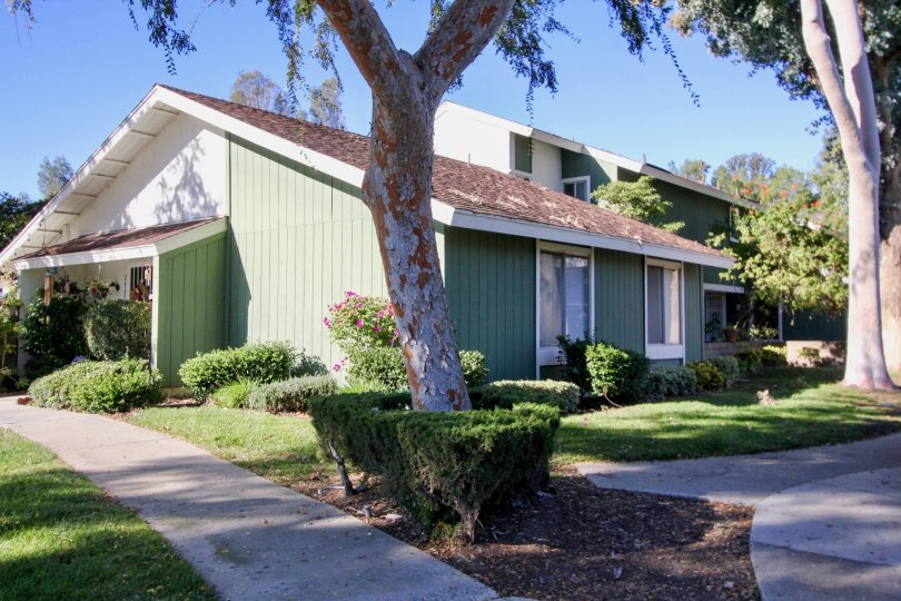 Shaded, green panelled townhome in the Village of Saun Juan, located in San Juan Capistrano.