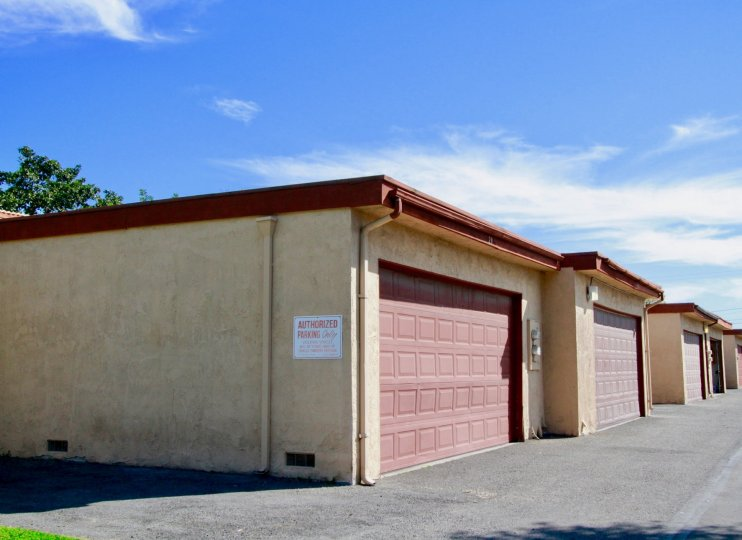 Garages with red doors in the La Linda Villas community on a sunny day.