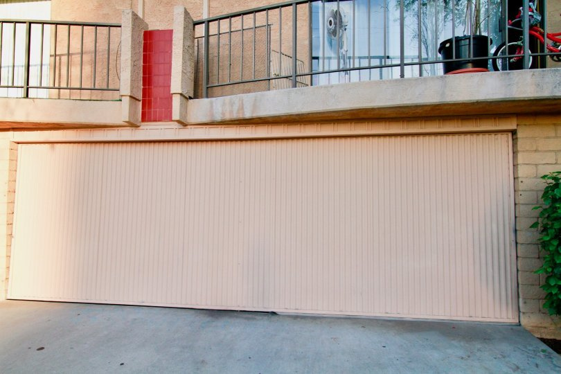 A view of a large garage door below a balcony in the La Plaza Real community
