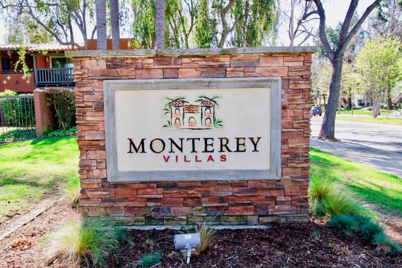 The brick sign of the Monterey Villas community on a sunny day.