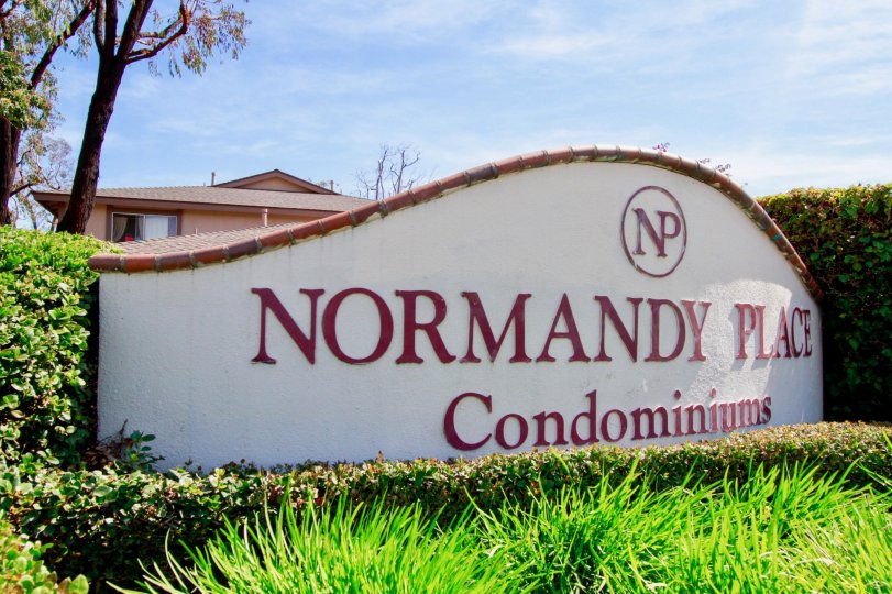The entrance board to Normandy place community with green grass around