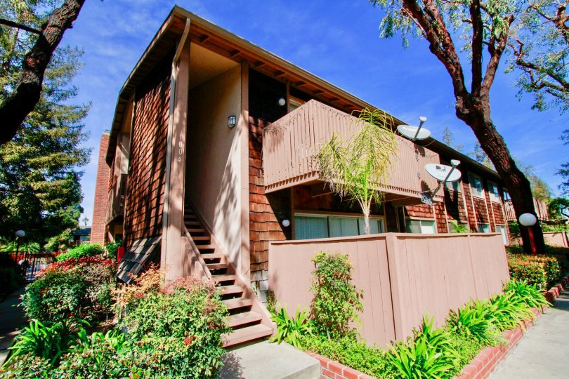 A small row house with a small compound and a staircase in the side in The Redwoods community
