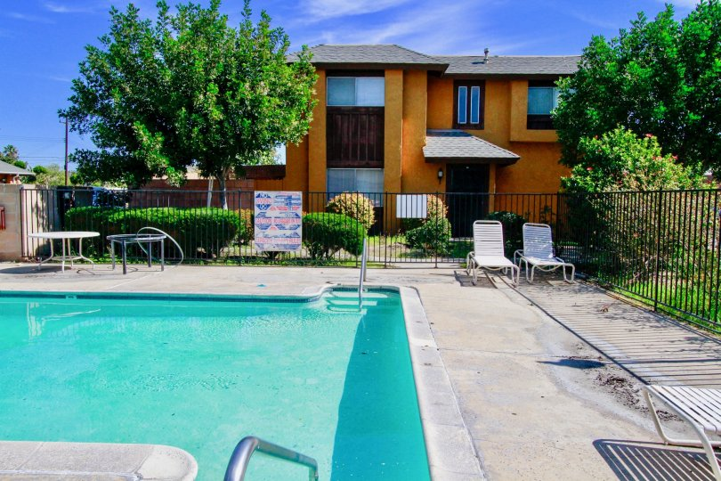 A great day in the Westvale Townhomes with a swimming pool and chair.