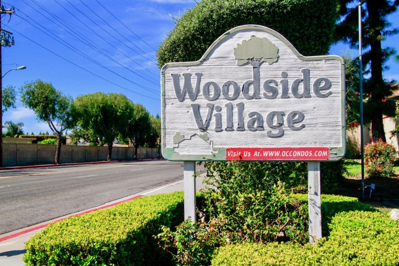 The woodside village board located at left side and a parallel road also there.