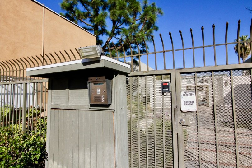 Meshed entry gate with high security fence and adjacent resident intercom box with spotlight in Pine Creek