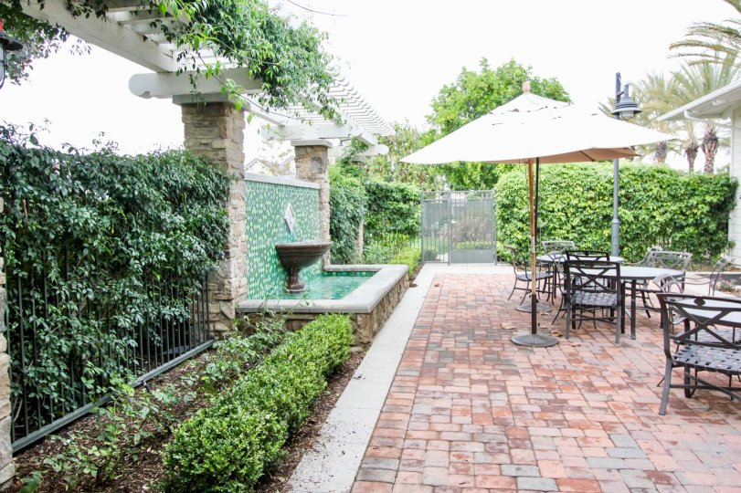 An overcast day in a patio in the Ainsley Park area with tables, umbrellas, and greenery surrounding the area